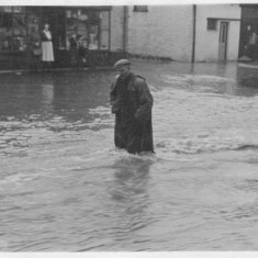 A villager struggles against the force of the flood, walking down the High Street