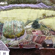 Fields, roads, hedges and bushes (as in the depiction of the Allotments, above) were embroidered either in situ directly on the calico, or using the same techniques as for the houses, or using materials with stitches applied for extra interest.
