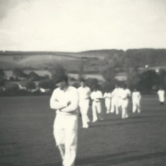Cricket team coming off field, John Berry leading.
