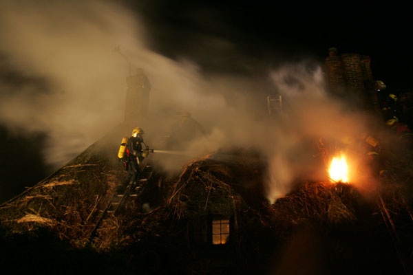 Firemen fighting the thatch blaze at Brook Cottages in January 2009