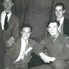 Four young men, one in uniform