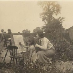 Girl painting in garden, mother looking