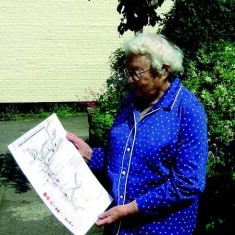 Margery Lambert, photographed in 2007, with her map of the shops and trades in East Meon in the 1920s