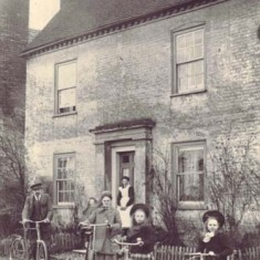 Nurse Kate Micklam with her bicycle, with her family, on the doorstep of Barnards, c 1903. She was the village midwife.