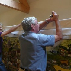 Rosemary Ryder and Charles Clayson fix the canvas to the oak frame