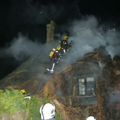 They began by creating a break in the thatch in order to prevent the fire spreading to the adjoining properties. (Petersfield Post photo)