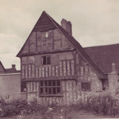 Tudor House from the south, showing the overgrown garden. The back of the shop extension is visible on the left the laundry outbuilding on the right.