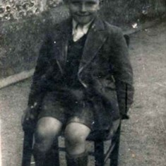 Alan Blackman sitting on the 'school chair'. His Headmistress during his early schooling, 1946 – 51, was the stern and somewhat miserable Mrs Gwendoline Hayes; she did manage to cheer and clap however when the Conservatives came to power in 1951. Of the Assistant Teachers, Alan remembers Miss Hastie, who often rapped childrens' knuckles with the edge of her ruler, and Mrs Paul, who, although well-liked, shared Mrs Hayes' nasty habit of blowing her nose then tucking the hanky up her knicker-leg.
