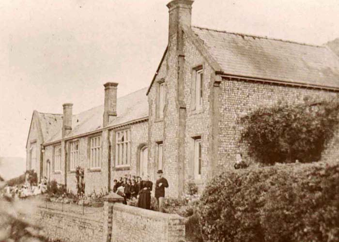 Groups of girls and boys outside their entrances to East Meon National School, 1900. William S. Tregear, headmaster, on the right.