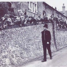 P.C.Dennis Thorne walks along the school wall, lined with children. Taken in 1949 by the New York Sunday News magazine.