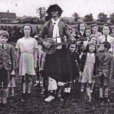 Schoolchildren with banjo 'minstrel'