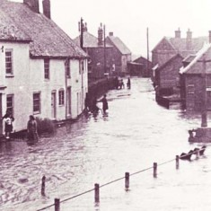Barnards and War Memorial flooded. Hazel Goddard is standing on the doorstep