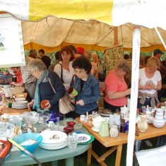 Crowded bric a brac stall. On the left, Hazel Rendle, one of the village residents running the stall.