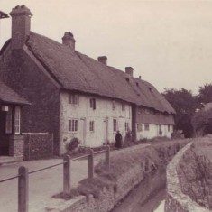 Hockley Cottage and narrow river. Old lady in black.