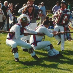 One of the early Country Fairs, the Morris Dancers join in the tug-of-war.