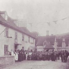 Staff and villagers gather outside the George Inn at a celebration, possibly Queen Victoria's Jubilee in 1887.