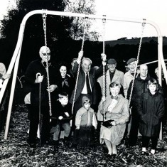 At the Opening of the Under-9s playground in the grounds of the Village Hall, 1996, standing, left to right, Jean Rockett, Joan Haines, Brigadier John Simpson (Chair of VH Committee), Monique Aldridge, Wilson Atkinson (Chair, Parish Council), Freddie Standfield, Peter Street, Rev Peter Wadsworth, (seated) Susan Hull, to her right, Zara Kitcher