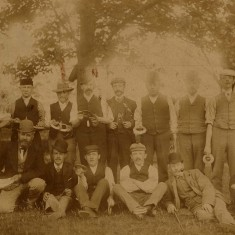 A very early photograph showing men holding what look like quoits