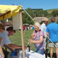 Pimms stall on The Green. Chris Gieves serves, Caroline Coe purchases.