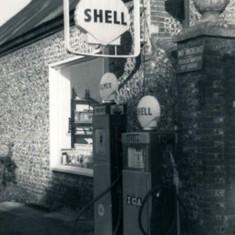 Petrol pump outside garage,.