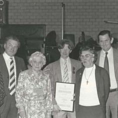 Presentation by Atkinsons to Ginger Phillips. L to R, Eileen A, Wilson A, Sarah (Wilson's mother), Ginger Phillips with certificate, Kate, Michael and Jane Atkinson