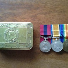 Edward Bone's medals and the tin in which they have been kept.