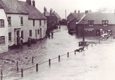 Flooding in East Meon, Hazel Pamplin on the steps of Barnards
