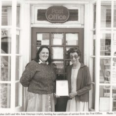 Jean Emptage with certificate and Judy Barber outside door of Post Office