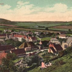 Hand-tinted post card, with the cottage  in the All Saints church yard. Young family picnicking in foreground.