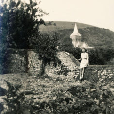Olivia Woodfield on wall with church behind, WWII