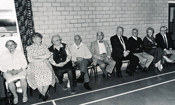 Residents sitting along the Village Hall wall