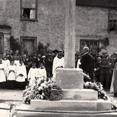 This shows the dedication of the new War Memorial commissioned by Rev. Thomas Heywood Masters and designed by Ninian Comper. y 11923, Masters was no longer vicar of East Meon and it is not known whether the clergyman to the left of the memorial is Masters or his successor Rev Crawley.