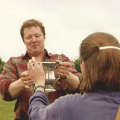 Rory Bremner collects the cup on behalf of his team.